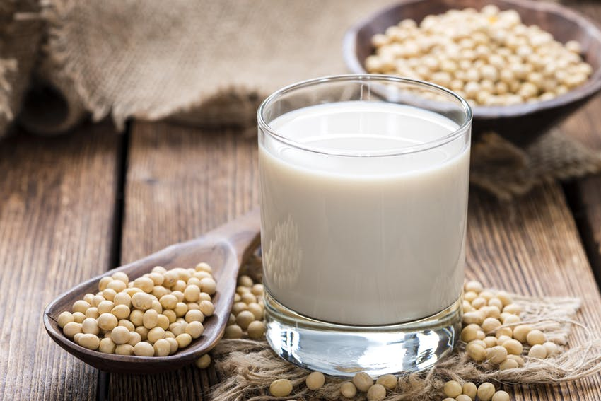 small glass of soya milk next to a wooden spoon of soya beans on a dark wooden table with decorative cloth