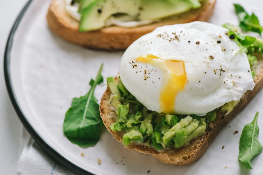 two slices of brown bread topped with smashed avocado, a poached egg with yolk oozing out with pepper and spinach on a white plate