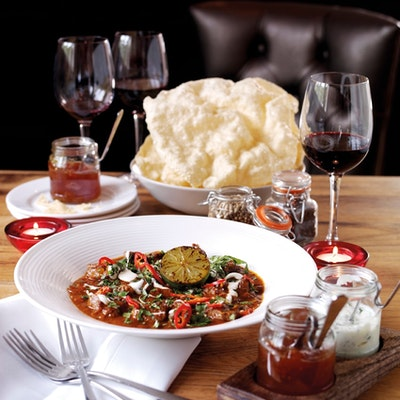dish of welsh lamb curry served on a table with two small glass jars of condiments a bowl of poppadoms and three glasses or red wine