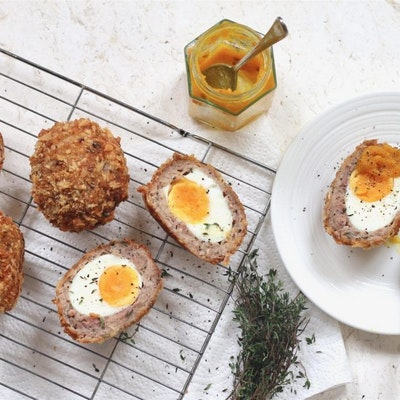 one scotch egg halved on a white saucer with a dollop of mustard and two scotch eggs halved on a wire cooling rack dusted with black pepper and fresh herbs