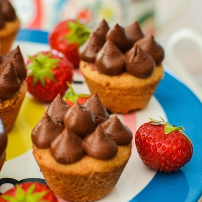five chocolate mousse and caramel shortbread cups on a blue plate with red strawberries