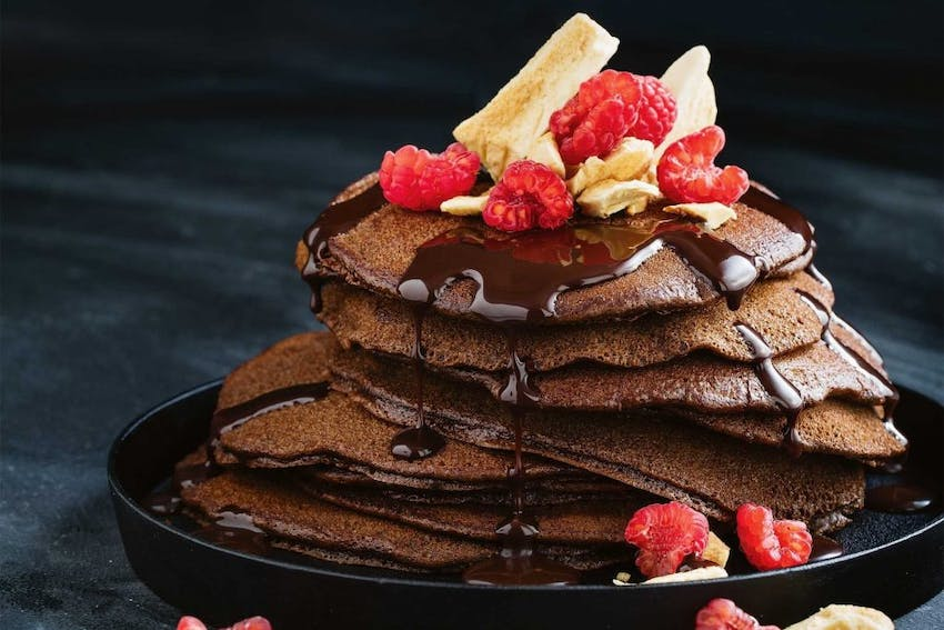 a stack of seven gluten free chocolate pancakes drizzled with chocolate sauce and raspberries