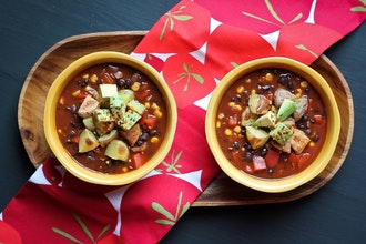 two bowls of vegan chilli with cocoa served on a wooden tray