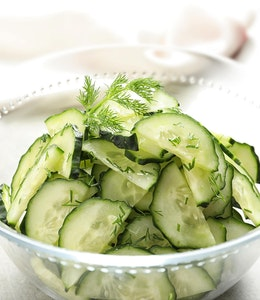 a clear glass bowl filled with green cucumber and dill salad