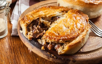pie baked in a brown dish 1/3 cut open and revealing beef and stilton meat and gravy filling