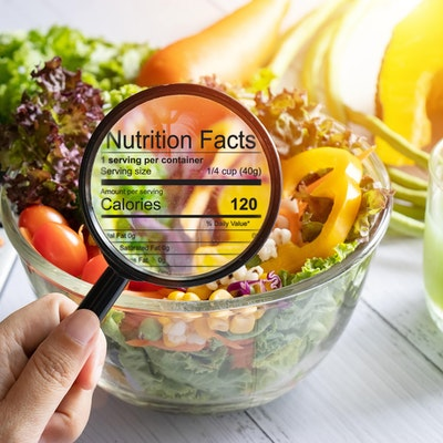 hand holding a magnifying glass illuminates nutrition and calorie information infront of a bowl of fresh crispy salad next to a calculator