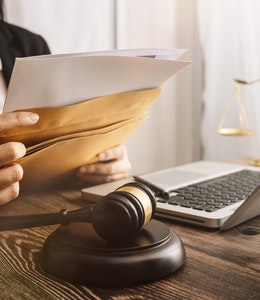 lawyer sits at a desk with laptop and dark wooden law gavel as she slips documents into a brown envelope