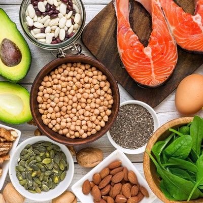 a birds eye flatlay of various nuts seeds beans and avocado spinach eggs and meat