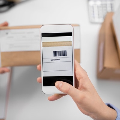 close up of womans hands with smartphone scanning barcode on a cardboard box