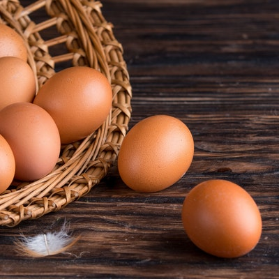 open wicker basket filled with eggs spilling out onto a dark wooden oak table and a small white feather