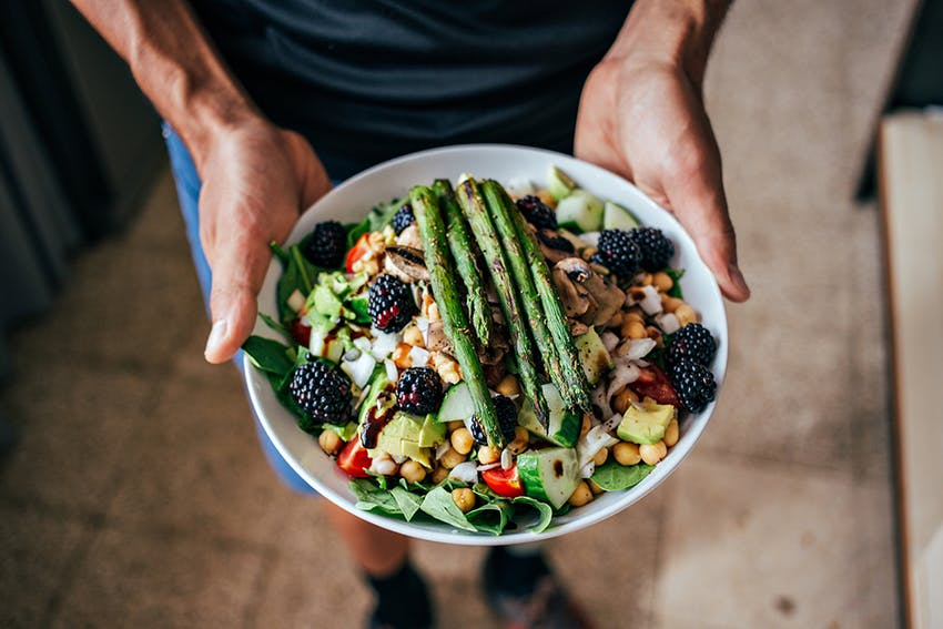 man holding a plate containing a varied and colourful salad topped with asparagus and blackberries