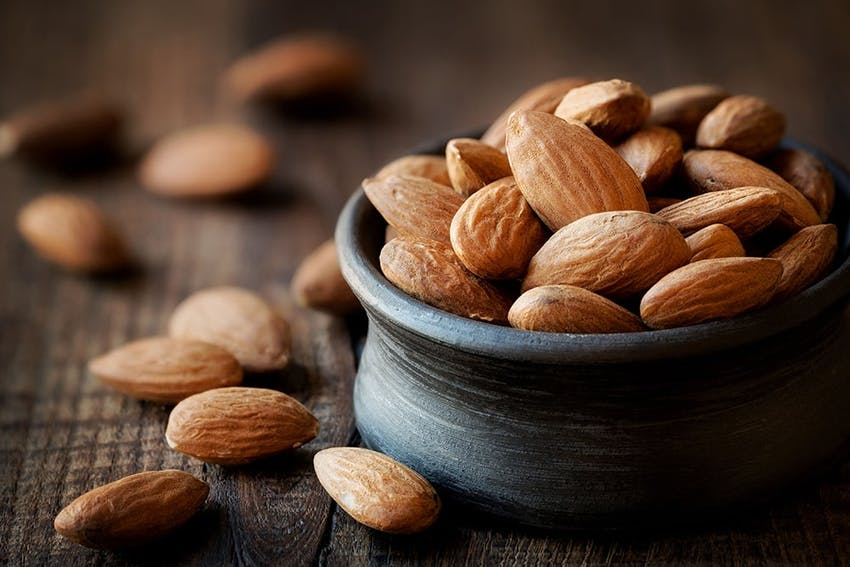 Small black rounded pot of almonds with almonds scattered around the pot on a wooden table