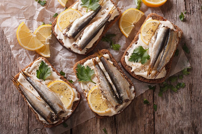 four slices of brown bread topped with two mackerel on a creamy dressing topped with fresh lemon wedges and herbs