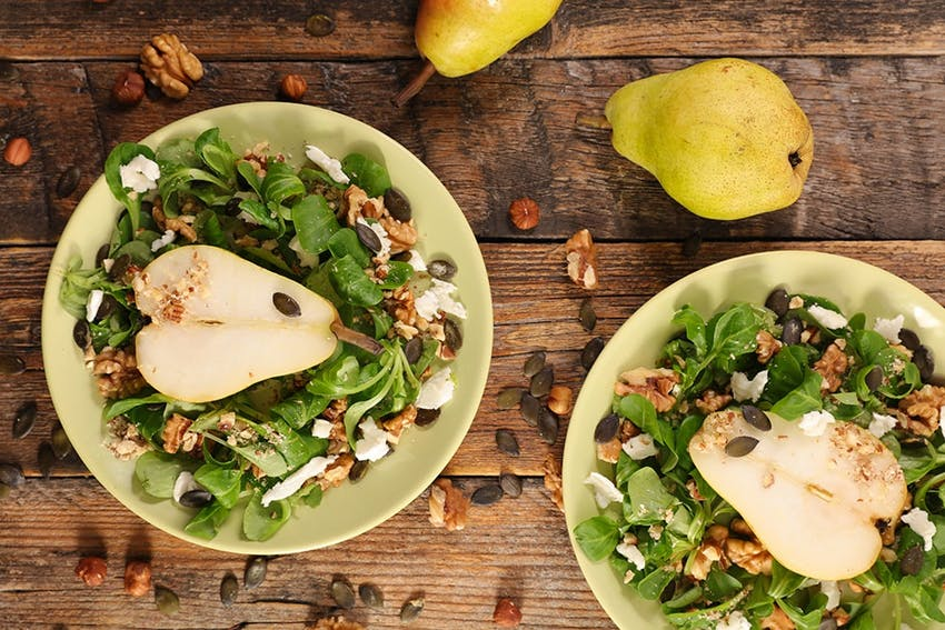 birds eye view of two plates filled with salad, pear, walnuts and cheese