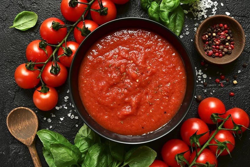 birds eye view of of a thick homeade tomato based sauce sprinkled with salt and pepper next to vines of cherry tomatoes, basil and a wooden spoon