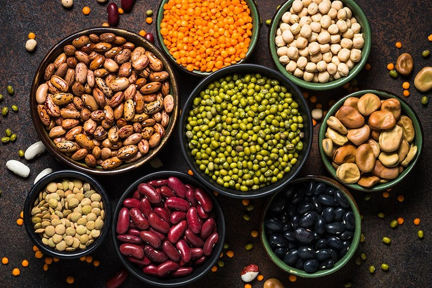 birds eye view of varying bowl sizes filled with nuts, lentils, peas and beans