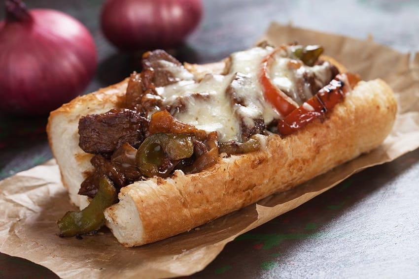 a crusty baguette with grilled chopped up steak, melted cheese, peppers and fried onions