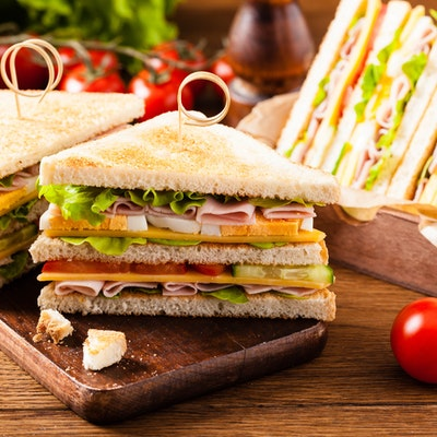 skewered double ham cheese and salad sandwich cut into small triangles on a small dark oak chopping board next to a group of vine tomatoes