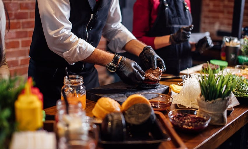 long wooden table with a range of plated foods set up for alive cooking demonstration where a man in a suit and black gloves places a joint of meat onto a chopping board