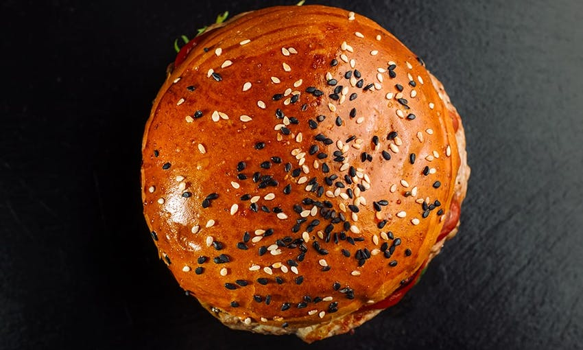 birds eye view of a golden brown brioche burger bun topped with black and white sesame seeds