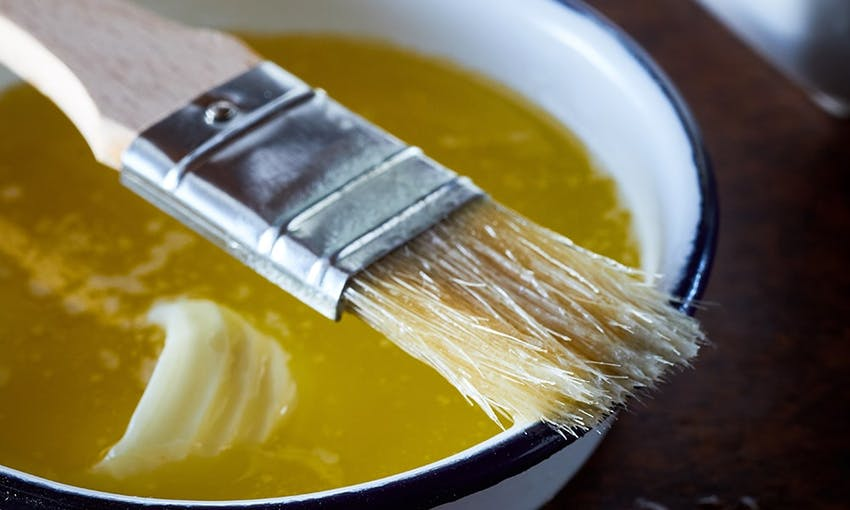 a bowl of butter melted and ready to be used for coating with a coating brush