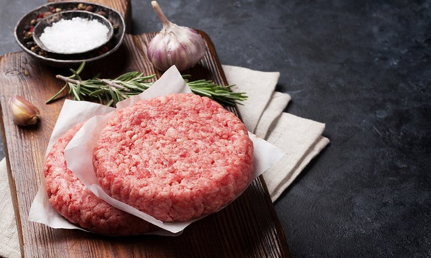 two raw circular burger patty's on top of a wooden chopping board ready to be seasoned