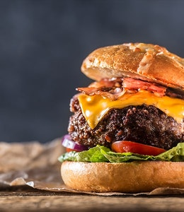 thick juicy beef burger with bacon lettuce tomato and american cheese in a bun topped with dressing