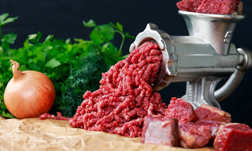 reddish meat being grinded in a silver meat grinder surrounded by fresh onion, chunks of red meat and fresh green herbs