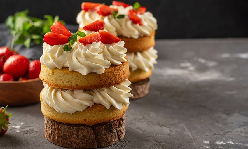 mini cakes with alternating layers of buttercream icing and sponge topped with strawberries and mini sprigs on mint