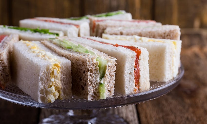 small rectangular cucumber, salmon and cream cheese and egg mayonnaise sandwiches on a tiered platter