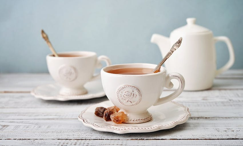 two teacups with a rose emblem on saucers filled with english breakfast tea with a brass spoon in the middle for stirring and a side of sugar cubes