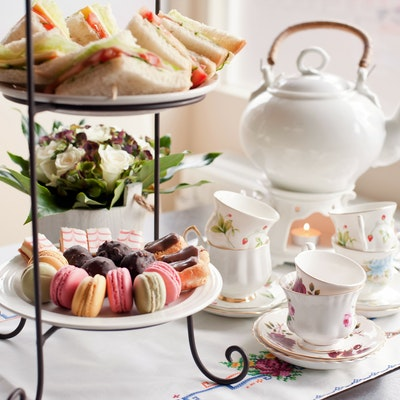 afternoon tea set up complete with a white chine teapot and teacup set on a white flowery tablecloth and a tiered plate stand with macarons, angel slices, eclairs and truffles on the bottom and mini sandwiches on top