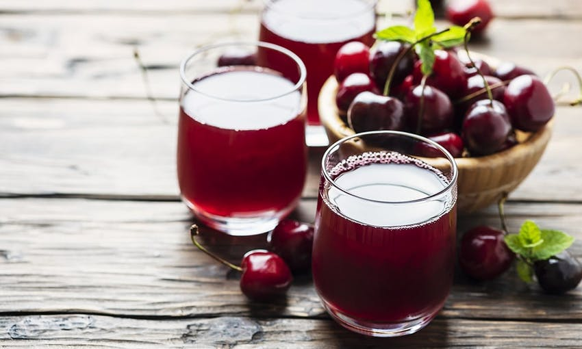 three glasses of dark red cherry juice next to a wooden bowl of dark red cherries on top of a wooden table