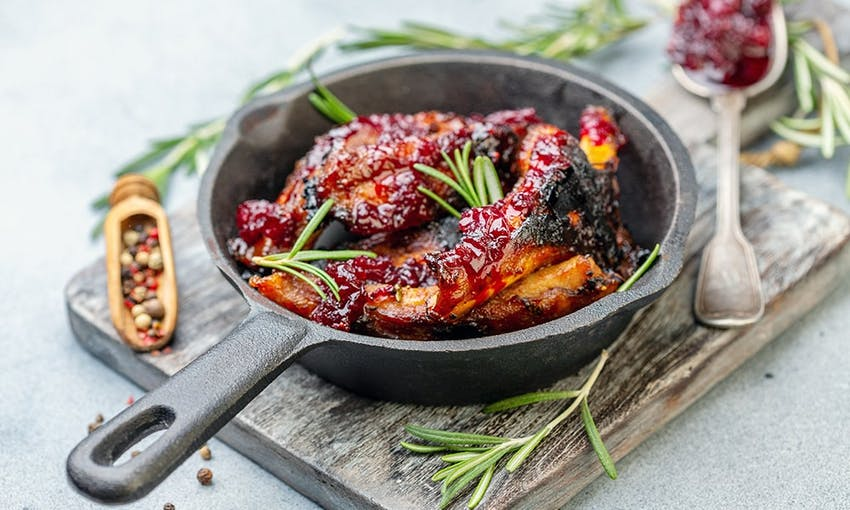 a small skillet with fried chicken wings glazed with a cherry reduction on top of a chopping board and decorated with fresh herbs salt and pepper