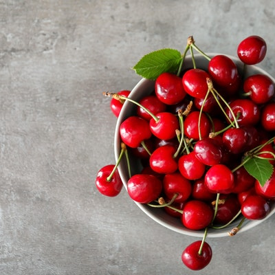 birds eye view of a bowl filled with red cherries on top of a marble table
