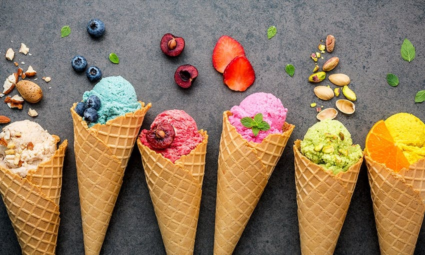 cream, blue, berry, pink, pistachio and orange flavoured ice creams in their cones decorated with fruit and nuts