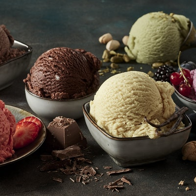 seven different colours and flavours of ice cream in stone dishes decorated with chocolate shavings and fruits