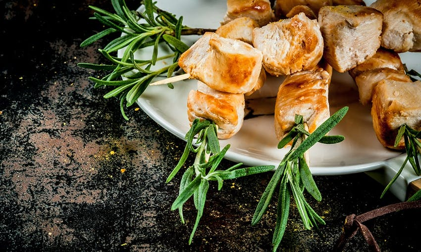 diced chicken breast cubes on rosemary skewers on a white plate on a dark wooden table top