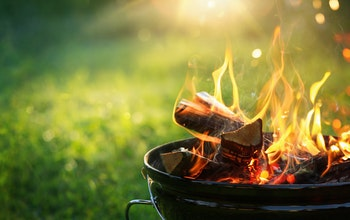 a lit freestanding barbecue with flames rising in front of a green grass back garden