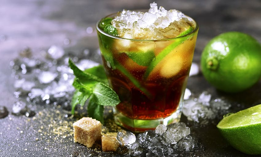 a small glass of ice tea with fresh mint topped with shaven ice surrounded by shaven ice, brown sugar cubes and fresh limes on a dark charcoal table top