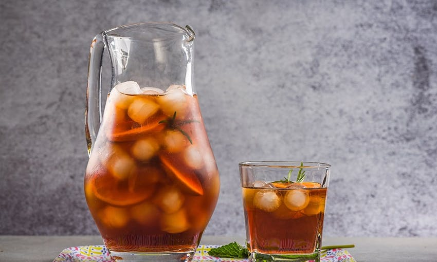a two litre jug filled with ice cubes, fruit and peach iced tea and next to a small glass of peach iced tea with fresh sprig of mint