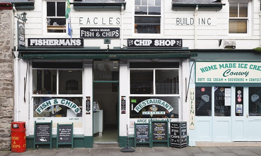 black and white traditional vintage looking storefront of a fish and chip restaurant with handwritten promotional blackboards at the front next to a home made ice cream shop