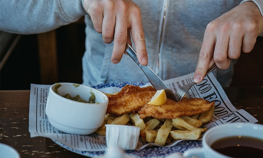 man in grey jumper tucks in to a plate of fish and chips on british newspaper with a side of mushy peas topped with a wedge of lemon