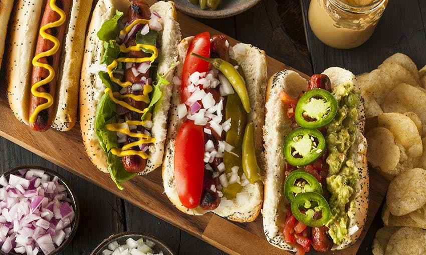 four hot dogs one topped with jalapenos and guacamole, one with gherkins and peppers, one with mustard and onions and the other with mustard next to crisps and a dish of onions
