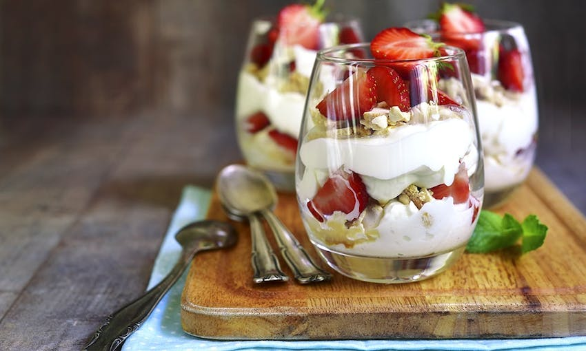 Three clear jars filled with eton mess made up of cream yoghurt strawberries and meringue on a wooden shopping board