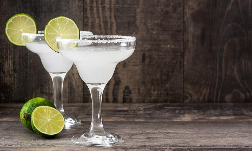 two short glasses filled with margarita with a salted rim and wedges of lime
