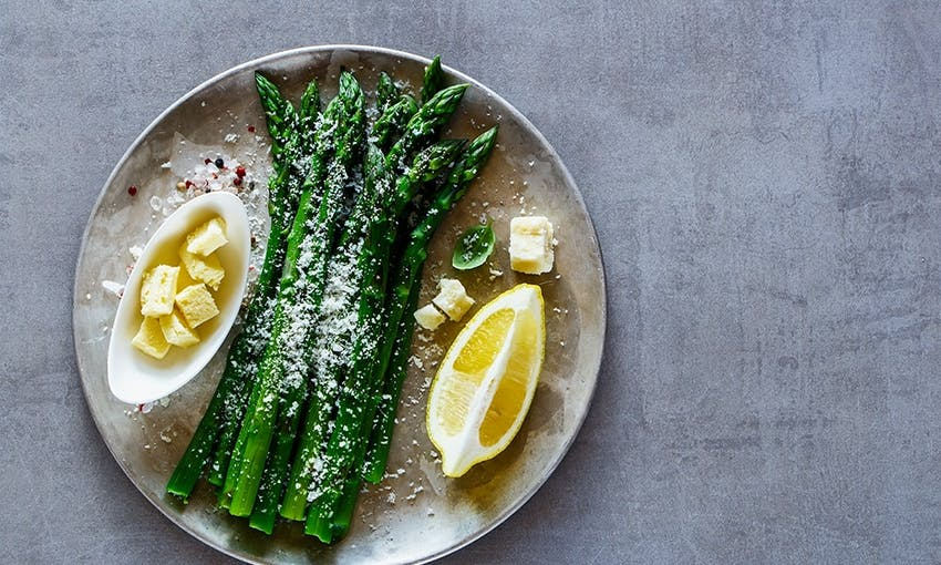 dish of asparagus sprinkled with parmesan served with cubes of butter and a wedge of lemon