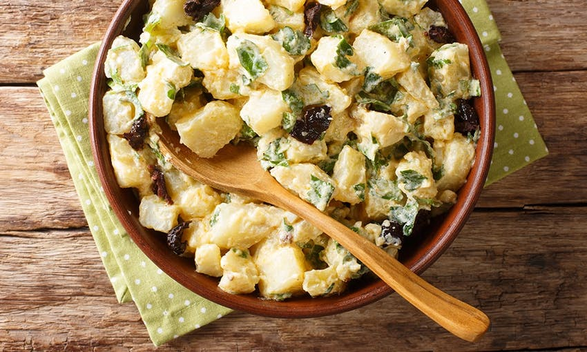 a bowl of creamy potato salad with fresh herbs and salad creamy with a wooden serving spoon