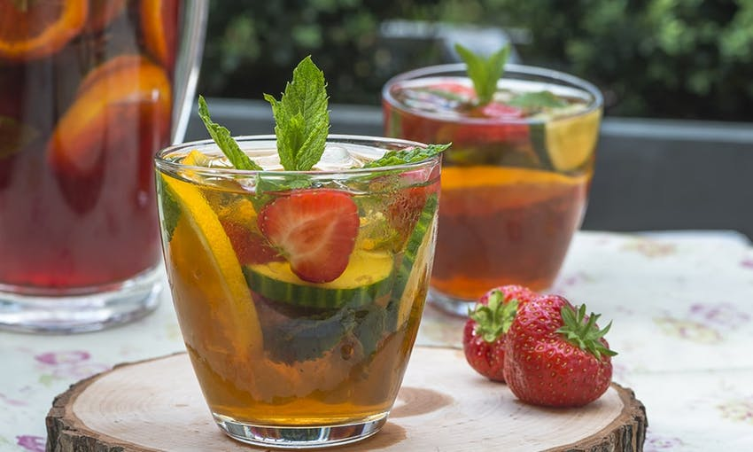 two clear glasses of pimms filled with fresh fruits on a summer dining table next to a jug of pimms