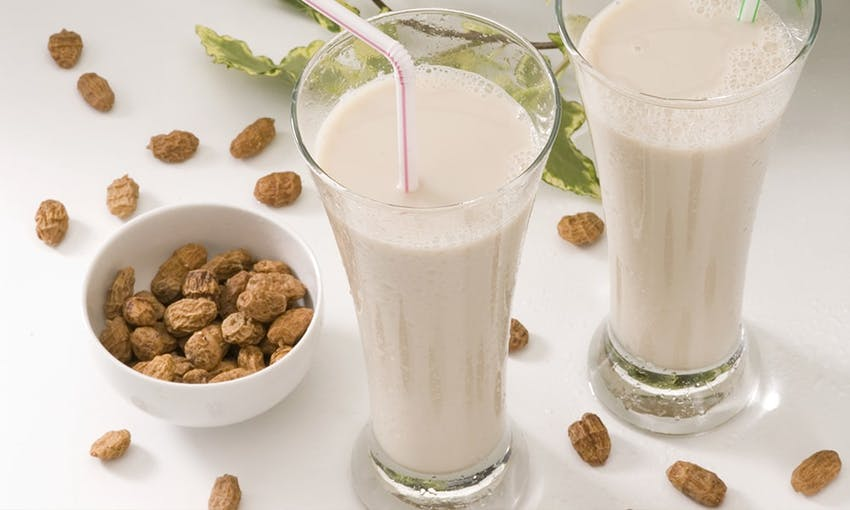 two clear glasses of tiger nut milk next to a small bowl of tiger nuts